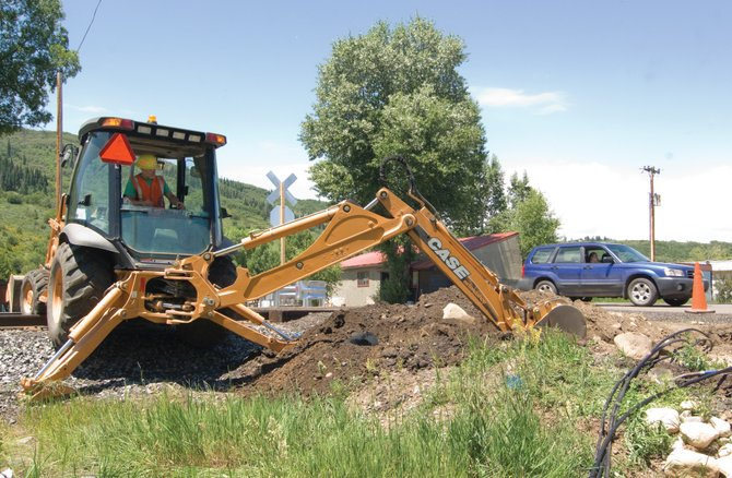 A car passes by as Union Pacific Railroad employee Rich Jepson uses a backhoe to dig a trench for cables while working to install new railroad crossing gates in front of the Fish Creek Mobile Home Park.