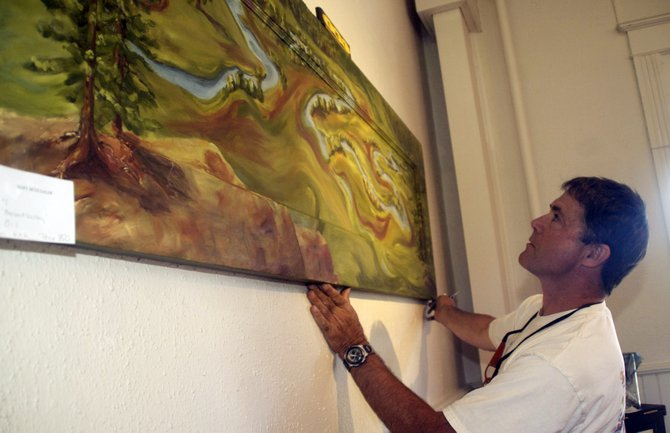 Dave Winters uses a level to ensure a painting is hung correctly Wednesday at the Depot Art Center in Steamboat Springs. An artist member show of the Steamboat Springs Arts Council opens at 5 p.m. Friday.
