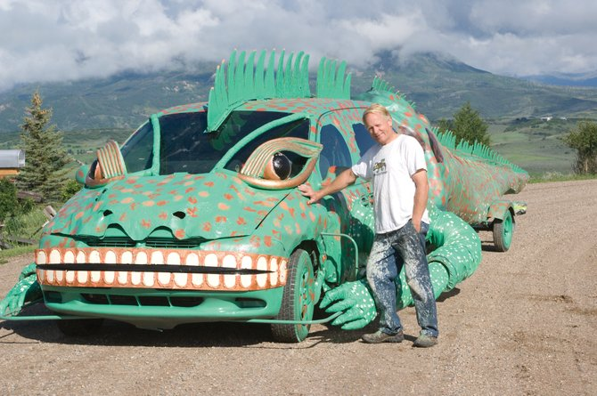 Charlie Holthausen stands next to his iguana car, a vehicle he has created using a minivan, trailer and items he's found in his home and in other places. He plans to unveil the car as a float Saturday in the Fourth of July Parade downtown.