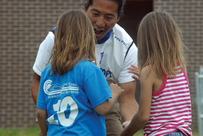 Jenkins Chan, of Seattle, plays a game of keep-away with Makyah Counts, 8, left, and Lael Conner, 6, on Thursday at the Boys & Girls Club of Craig. Chan was part of a group of 28 riders traveling across America for Journey of Hope, hosted by Push America, which raises money and awareness for people with disabilities.
