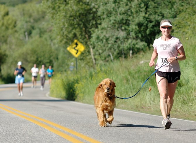 Duncan, a golden retriever, leads the way for Steamboat Springs resident Linda Casner near the end of Sunday's 10-kilometer race at the Mountain Madness Steamboat Springs Running Series event.