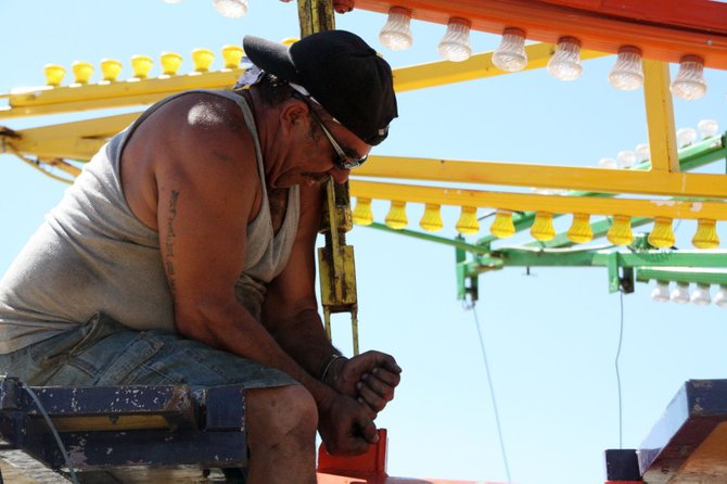 Eddie Martinez, of Brown's Amusements, sets up a ride Monday at the intersection of Fourth and Ranney streets. A small carnival is Wednesday through Saturday.