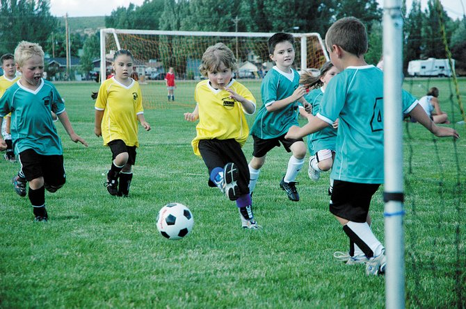 Thayne Kitchen gets his kicks in during a game Tuesday night at Woodbury Sports Complex. The Craig Parks and Recreation youth soccer league started Monday night.