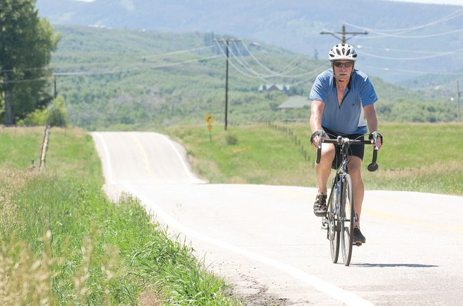 Cyclist Tom Dougan rides his bike along Routt County Road 14 on Monday. The Routt County Board of Commissioners held a meeting Monday evening to discuss the shared use of county roads.