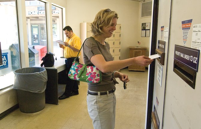 Steamboat Springs resident Heidi Pritchard drops her mail into a box at the post office branch in Sundance at Fish Creek shopping center Wednesday afternoon. A U.S. Postal Service plan states that sometime before Thanksgiving, all 2,584 boxes will be moved to the downtown post office location, but some hope for an alternative.