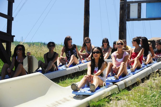Denver Broncos cheerleaders line up to ride down the Alpine Slide on Howelsen Hill.