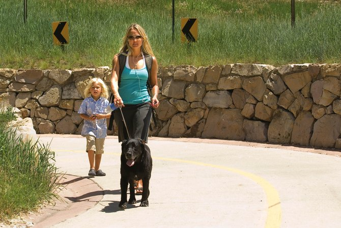 Susy Demusis, right, and Giovanni Demusis walk their dog, Fife, along the Yampa River Core Trail on Monday afternoon. The city has expanded off-leash regulations to allow dogs to play unleashed at Rita Valentine Park and Lower Spring Creek Pond from dawn to dusk, seven days a week.