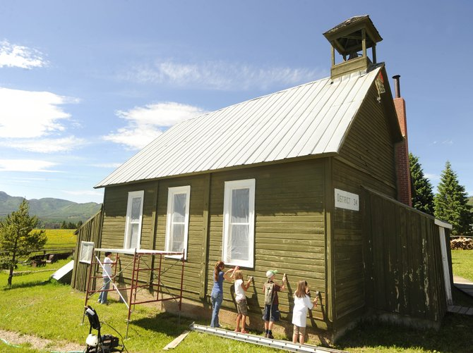 Wheeler family and friends, from right, Anne Mitchell, Jacob Mitchell, Shayna Mitchell, Claire Farnsworth and Mitchell Timothy scrape paint Thursday at the historic Hahn's Peak Schoolhouse. More than 30 people are working to repaint the schoolhouse with its original white color.