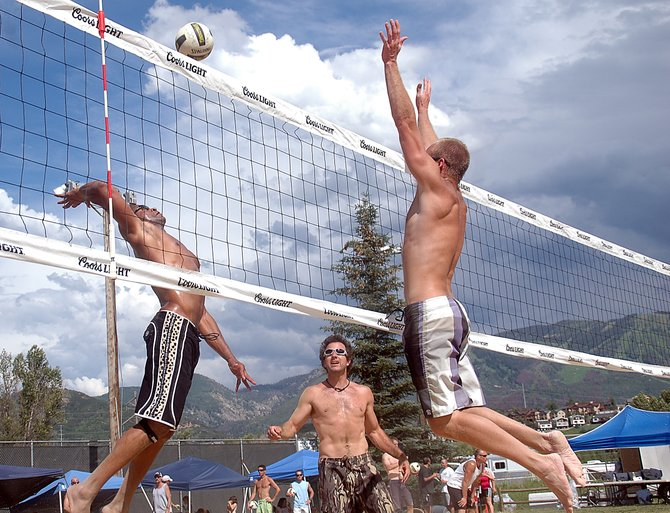 Chip Hollis, left, swings to get a spike past Derran Cannon on Saturday at the Steamboat Doubles Volleyball Tournament at Howelsen Hill.