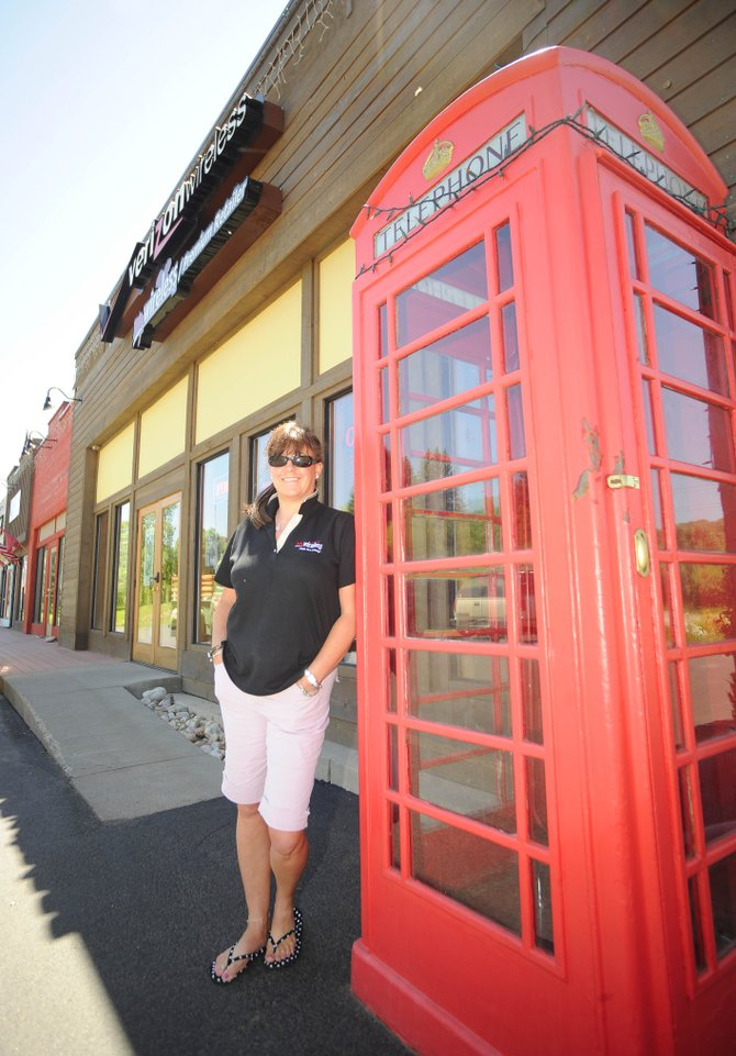My Wireless employee Lisa Leach stands by the vintage London-style phone booth in front of the store in the 600 block of South Lincoln Avenue. The booth was home to a life-size Superman mannequin, but it recently was stolen.