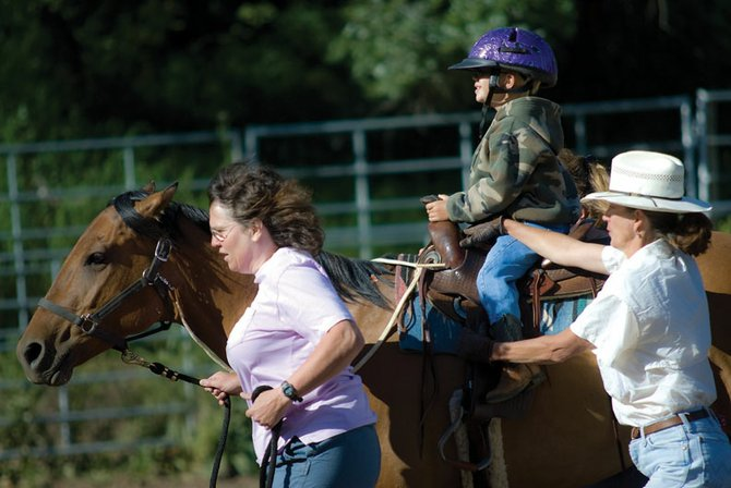 Josiah Petersen, 6, of Craig, rides a horse Tuesday morning led by Linda McIntosh, left, and physical therapist Carol Sitlington at a ranch south of Craig. Petersen is participating in a summer program for special-needs students to keep them from regressing.
