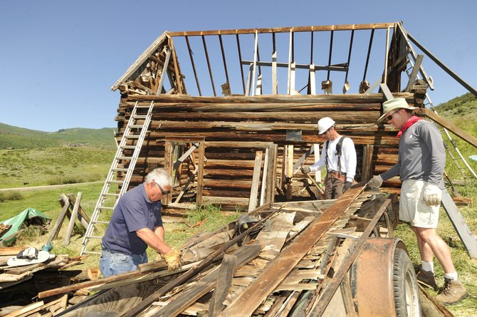 Workers, from left, Jim Williams, Scott Kemp and Brian Edwards work Wednesday on the restoration of the Diamond Window Cabin in Stagecoach. Historic Routt County hopes the preservation of the more than 100-year-old cabin will cause people to take on other restoration projects.