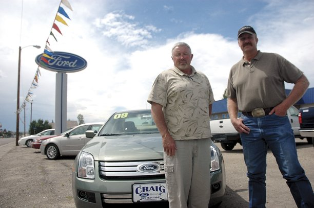 "Jeff Corriveau, left, and Burl McMillan, salesmen for Craig Ford, stand next to one of the new cars on the Craig Ford lot that could be eligible for a ""cash for clunkers"" swap. ""Cash for clunkers"" is a new federal program that provides a $3,500 to $4,500 credit to consumers on new vehicle purchases if they trade in an old vehicle with low gas mileage."