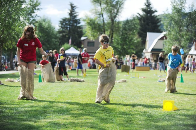 Boys & Girls Club of Steamboat Springs junior staff member Maggie Kriz, left, races potato sacks with 10-year-old Wyatt Gray, middle, and 7-year-old Lowen Epstein on Tuesday during the club's grand opening on the field at Eighth and Pine streets.