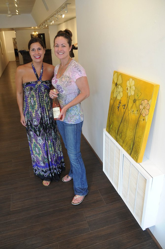 K. Saari Gallery owner Kimberly Saari, left, and bistro c.v. owner Katy Vaughn show off a bottle of the wine that will be featured during Friday's show.