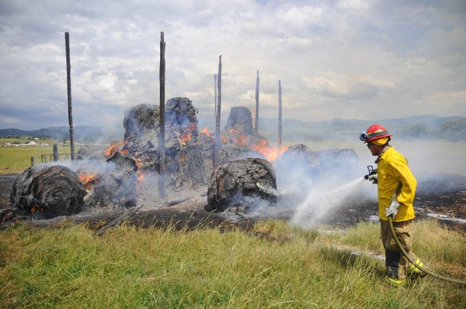 Steamboat Springs Fire Rescue firefighter Brian McGovern sprays water on the perimeter of a fire that destroyed a barn and the hay inside it Thursday at the Daughenbaugh ranch on Routt County Road 44 along the Lower Elk River. The fire was caused by lightning.