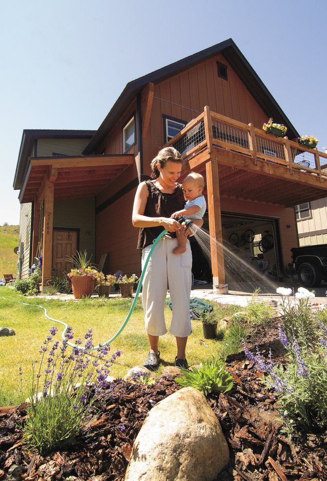 Homeowner Kathy Woodford holds 1-year-old Kira while watering the front yard of her Red Hawk Village home in Stagecoach. Kathy and her husband, Scott, bought the home at the top of the market, and have watched as prices of other homes in the community have dropped.