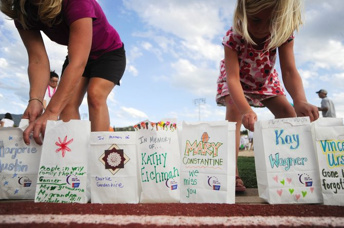 Seven-year-old Annika Belshaw, right, sets up luminaries with Steamboat Springs resident Sarah Peed on Friday during the Relay For Life event in Steamboat.