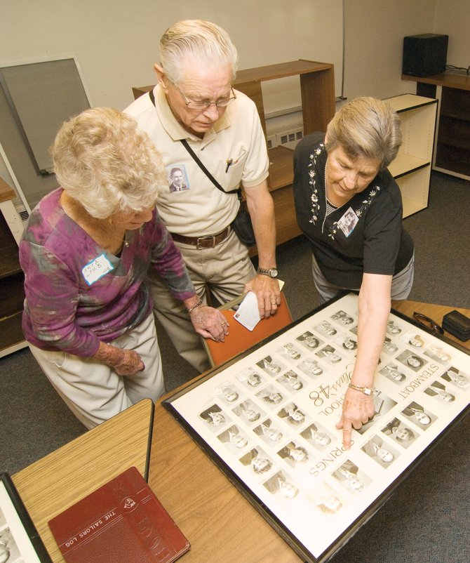 "Roberta (Lamb) Svendsen points out a classmate while visiting with her brother, Joe ""Weldon"" Lamb, and his wife, Arta, at a check-in party for the Steamboat Springs High School classes of 1948 and 1949 reunion."