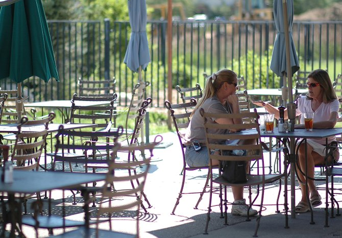Christine Lindmier, left, and Barb O'Connor eat lunch around noon on an otherwise empty patio at Rex's American Grill and Bar in Steamboat Springs. Restaurant owner Rex Brice said even businesses that rely heavily on locals rather than tourists have suffered in the economic recession.