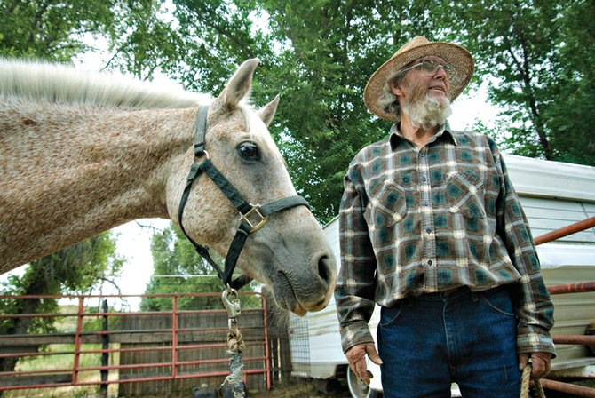 Lex Burton stands with his horse, Abu, outside his home in north Craig. Burton has kept horses on his property off and on since he moved there in 1965, but he recently was informed by the Craig Police Department that he would have to remove them or be fined.
