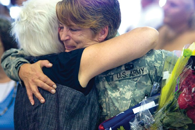 U.S. Army Sgt. Kathy Weiher receives a hug from her mother, Ann Kidder, on Friday at the Yampa Valley Regional Airport. Weiher had just returned home from Iraq and was greeted by family, friends and members of the Veterans of Foreign Wars Post 4265 and American Legion Post 62 as part of a new program to celebrate the return of Iraq veterans.