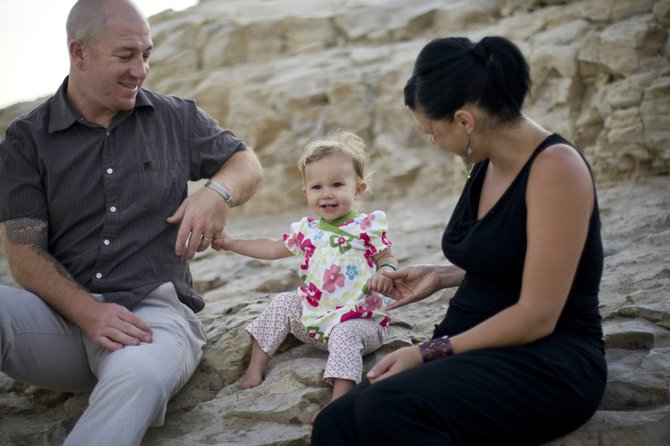 Max Halterman sits with his wife, Samara, and their daughter, Sylvyanna, at the Natural Bridges State Beach in Santa Cruz, Calif. Halterman, along with other Oak Creek natives, has created a successful business in Santa Cruz importing silk and other goods from Vietnam.