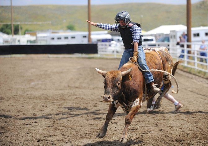 Thirteen-year-old Kaiden Decker, of Hayden, rides a bull Saturday during the Routt County Fair calf riding competition. His ride lasted 3.89 seconds.