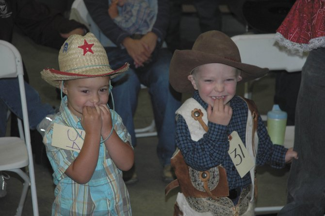 Three-year-old Sam Mosciaro, of Hayden, right, and Kodiak Byron, 2, also of Hayden, try to charm the judges during the cutest dimples contest Sunday at the Routt County Fair's Pretty Baby Contest.