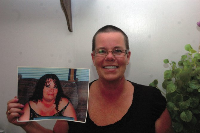 Debbie Ciani, of Craig, holds up a picture of herself before she cut off her hair to donate to Locks of Love. She said she cut her hair for her friend, Janice Nicoletto, who lost her hair because she is undergoing chemotherapy.