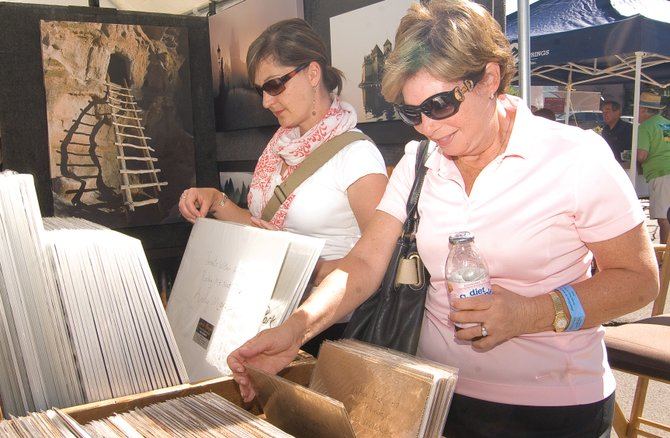 Maxine Urheim, right, and Carrie Olsen look through photographs by Andy Marquez during the Steamboat All Arts Festival's Yampa River Art Stroll on Friday morning. The festival continues today.