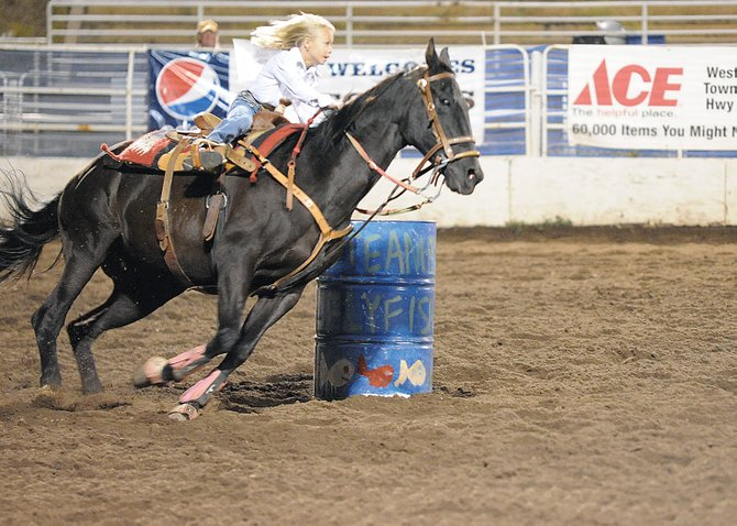 Paige Barnes rounds the final barrel Saturday during Pee Wee barrel racing at the Steamboat Springs Pro Rodeo. Paige won the night&#39;s race, which lifted her into a tie with defending champion Amber Salazar. The two young girls rode all summer in the Steamboat rodeo and shared the championship belt buckle.