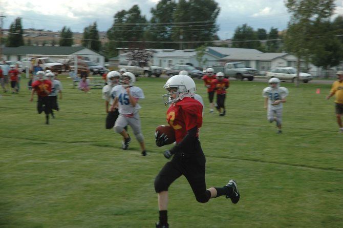 Shandon Hadley is a blur as he runs past the Colts. Shandon, 12, paced the Cardinals by scoring two touchdowns, including running one back on the opening kickoff, during Tuesday's opening night game of the Doak Walker youth football season.