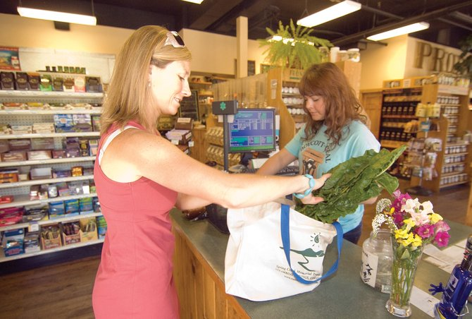 Cara Marrs loads up her reusable bags at the Bamboo Market Health Foods in Steamboat Springs after being checked out by Kelli Sawatzke. Local stores, including larger chains such as City Market and Safeway, are taking part in the Colorado Association of Ski Towns Reusable Bag Challenge.