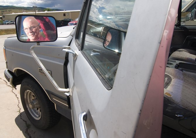 Jeff Schwebke, general sales manager at Steamboat Motors, is reflected in a mirror while he stands next to a 1991 Ford F-150 XLR Lariat pickup that his lot took in as part of the Cash for Clunkers program. Steamboat Motors is extending the government's program on its own dime. The government-sponsored program ended Monday.