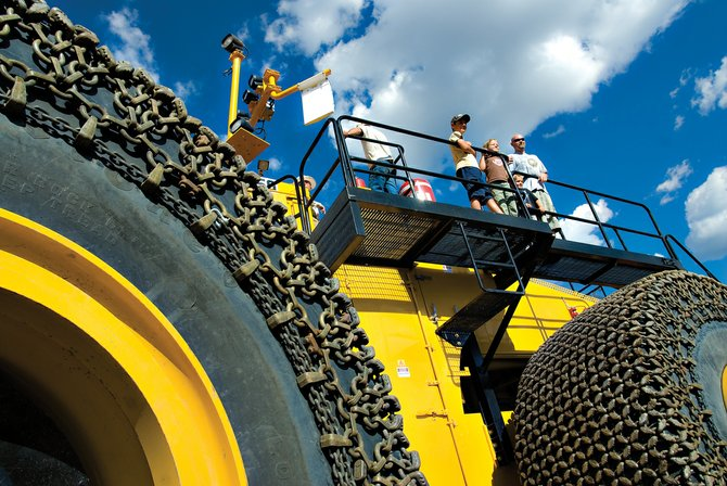 From left, Derek, 13, Alex, 7, Baryn, 5, and Fletch Suessmier look from the top of Trapper Mining's new front-end loader. The loader, created by LeTourneau Technologies in Longview, Texas, is one of five in the world and the largest of its kind. Each tire costs $100,000 and is covered in chains costing $40,000.