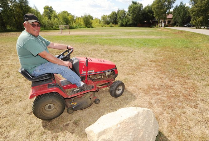 Marty Boomgarden says he has been voluntarily mowing the unofficial Riverside neighborhood park for 28 years. The neighborhood residents are feuding with the city about how the city-owned parcel should be maintained.