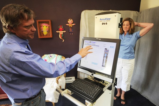 AccuView founders Kris and Jim Stouffer demonstrate Friday how their multi-imaging system photographs the body to create a record of moles.