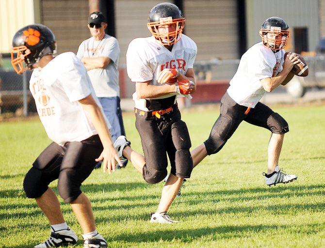 Graig Medvesk, right, works behind his offensive line  Wednesday as the Hayden High School football team practices. Medvesk, a junior, will take over the quarterback position.
