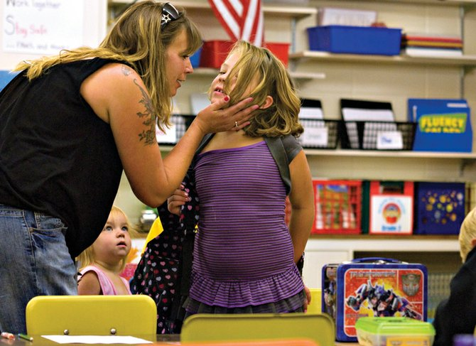 Tonja Reed kisses her daughter Cassie goodbye before class begins Monday morning at Sandrock Elementary School. Most students across the Moffat County School District began the new school year Monday.