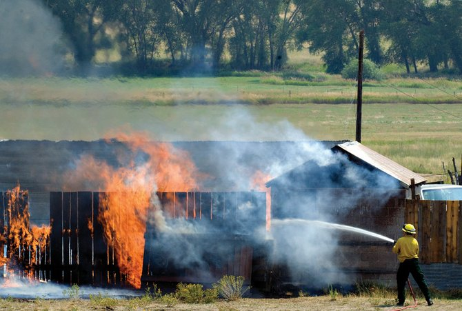 A Craig Fire/Rescue firefighter douses a burning outbuilding Tuesday on resident Mitch Shepherd's property near mile marker 98 on Colorado Highway 13 north of Craig. A fire department official said the fire began after Shepherd started burning trash on his property and lost control when winds picked up.