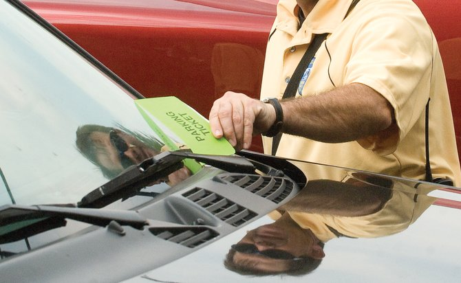 Code enforcement officer Shane Jacobs places a parking ticket on a car in downtown Steamboat Springs in 2009.