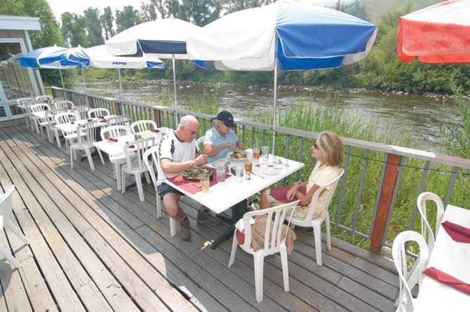 Russ Wohlers and his wife, Linda, seated on the far side of the table, visit with Sharon Beaupre on the deck of the Steamboat Yacht Club in downtown Steamboat Springs. The well-known restaurant will close its doors for the last time Sept. 12.