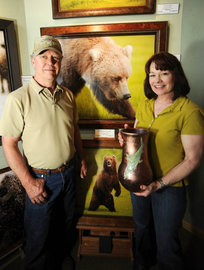 Sleeping Giant Gallery owners Don Tudor, left, and Cully Kistler went to Alaska in June to take pictures of and paint wildlife. Tudor's photos and Kistler's paintings will be on display at a reception Friday at Sleeping Giant Gallery. Kistler is holding pottery by Brown Cannon, who also is featured in the First Friday Artwalk reception.