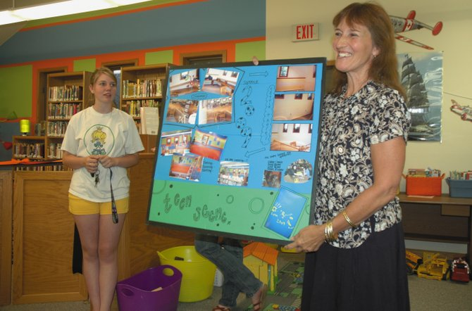 A summer's worth of work went into the new teen corner at Hayden Public Library. Library Director Ana Lash, right, shows off photos of the process at a ribbon-cutting Thursday. Lysa Valora, left, helped design and create the corner.