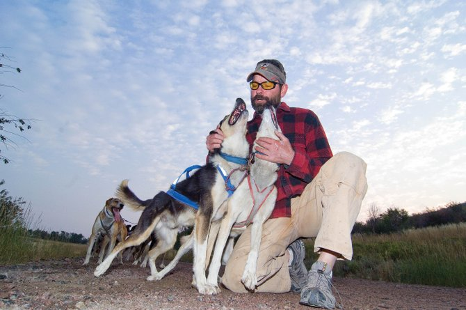 Tom Thurston visits with his lead dogs during a stop at the halfway point of a training run on a county road near Oak Creek.  Thurston uses the stop to water the dogs and train them for what life will be like on the trail during races like the Iditarod.