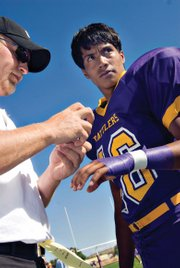 LSRV football assistant coach Jesse Herold, left, tapes up the arm of freshman Manuel Quinteros shortly before the game against visiting Hanna Elk Mountain Medicine Bow Junior Senior High School. The Rattlers lost, 68-28.