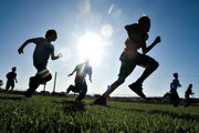 Isaac Filip, 11, center right, plays football with his friends while his two older brothers play in the varsity game. Filip, a sixth-grader, played on the junior varsity team, which won, 49-25.