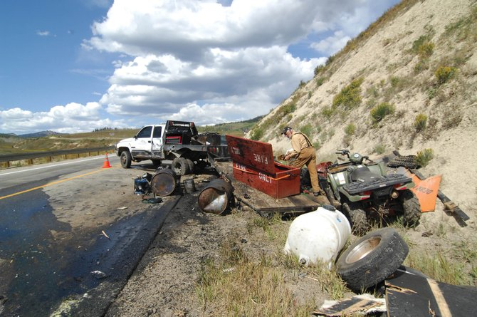 Jerry Neff, a crew supervisor with West Range Reclamation, cleans up after a semitrailer that had drifted into his lane sideswiped the truck he was driving. The eastbound truck hit three cars before coming to a stop on U.S. Highway 40 just past the Walden turnoff.