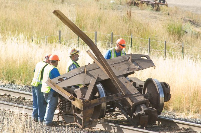 Union Pacific Railroad employees examine a set of wheels left on a track after they pulled away from a rail car early Friday morning just south of downtown Oak Creek. The car, which weighed 125 tons, won one of 140 cars on the train. There were no injuries and the cause the suspected mechanical failure is still under investigation.